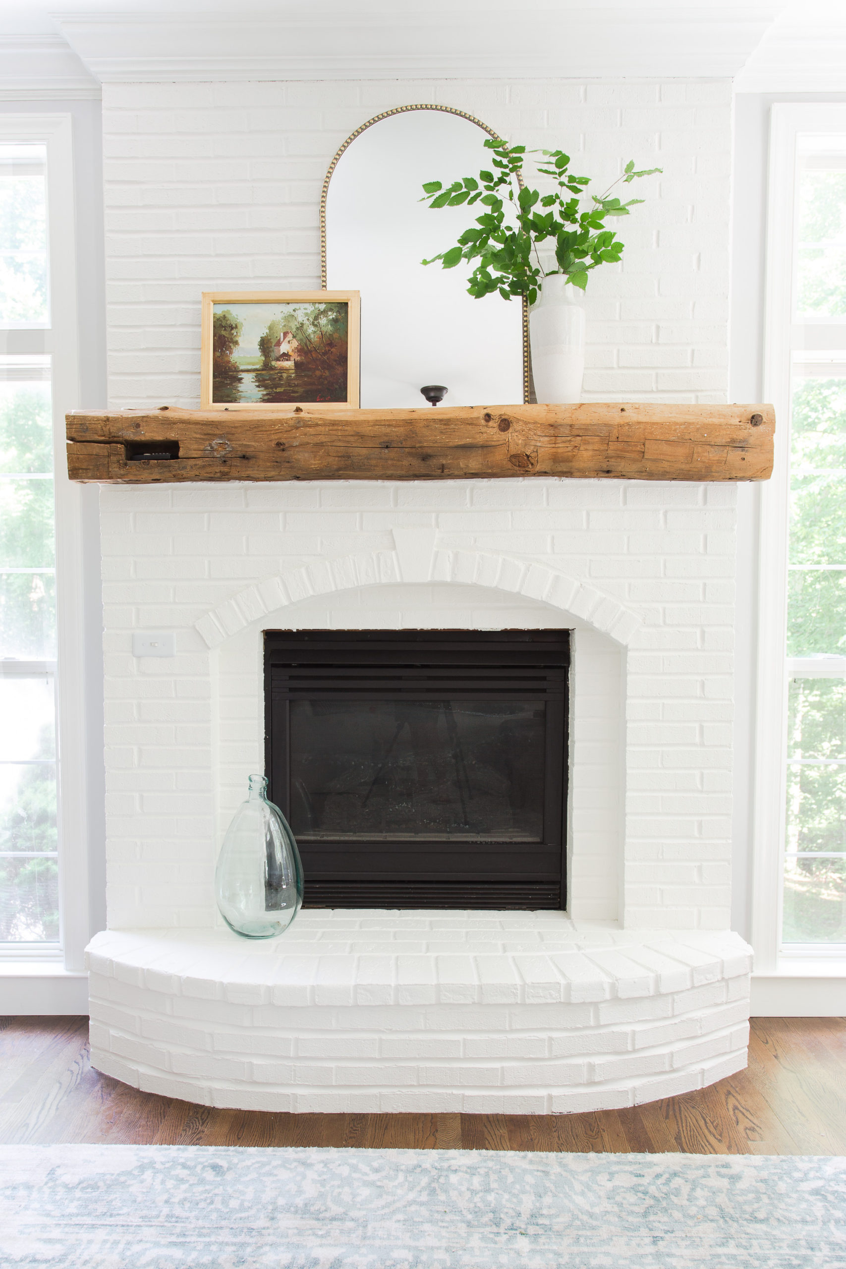 White brick fireplace with wood mantel and gold arched mirror