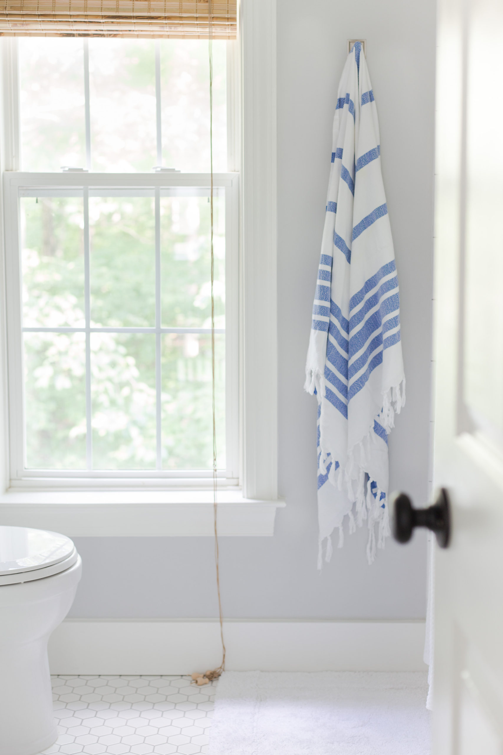 white bathroom with gray walls and a blue and white towel hanging from a hook