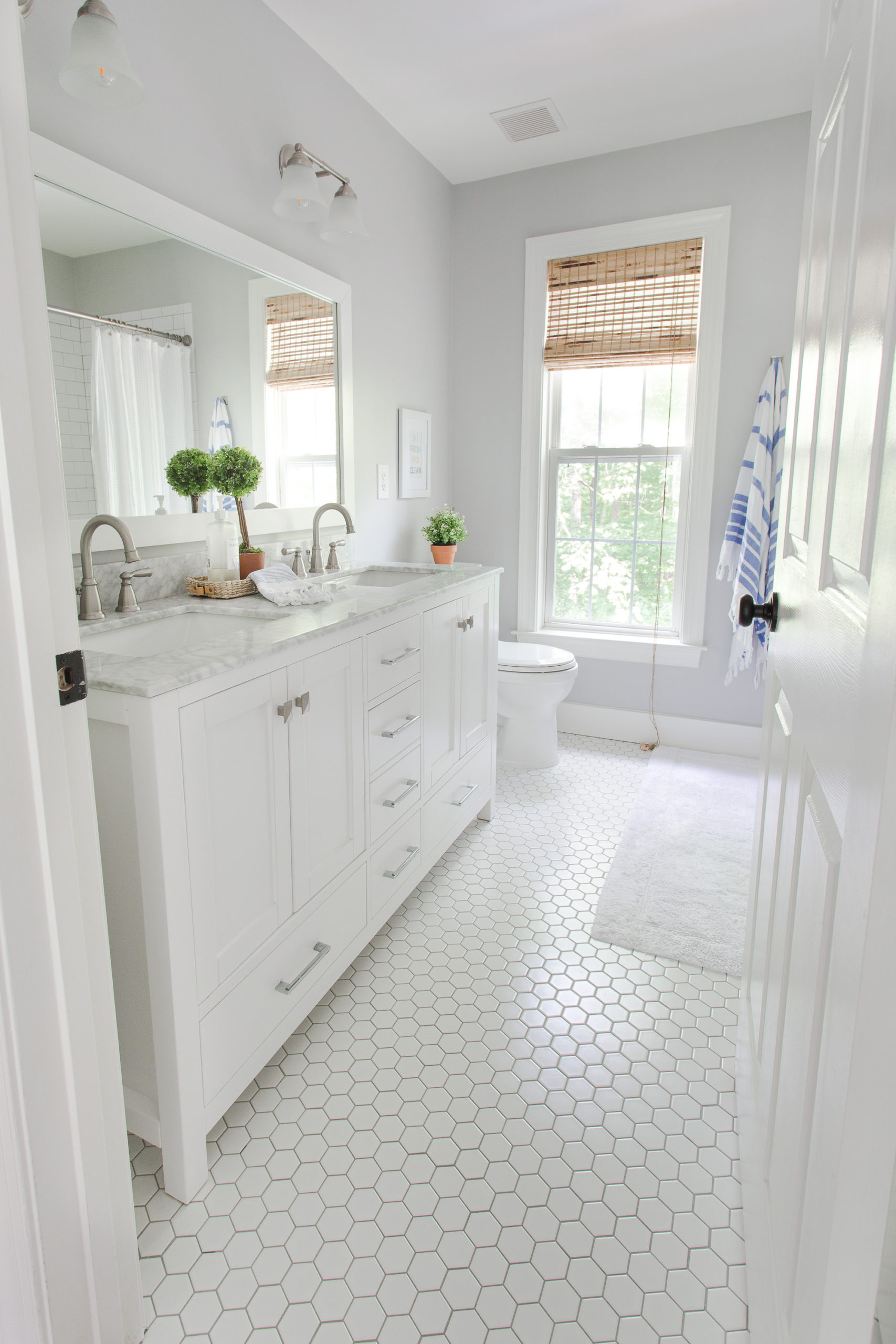 white bathroom with hexagon floor tile and gray walls.