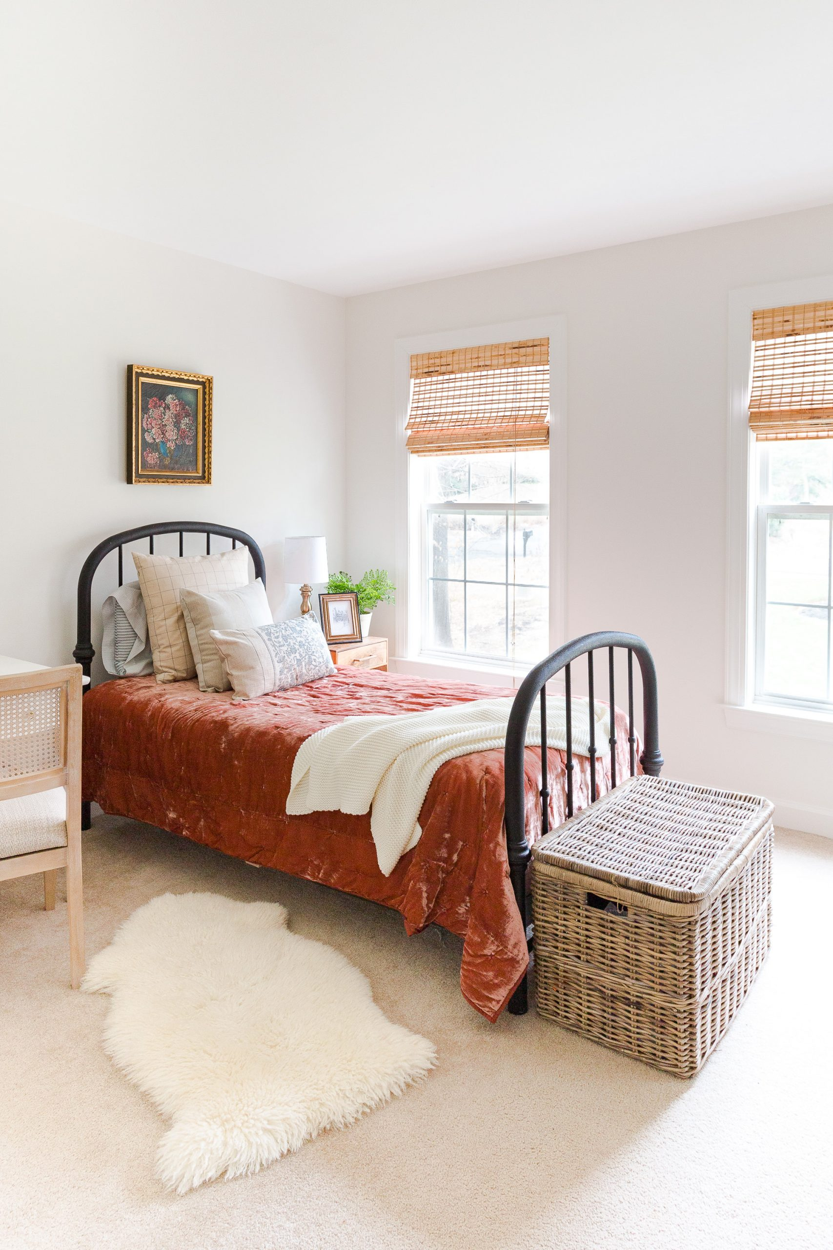 white bedroom with black iron bed and red velvet comforter