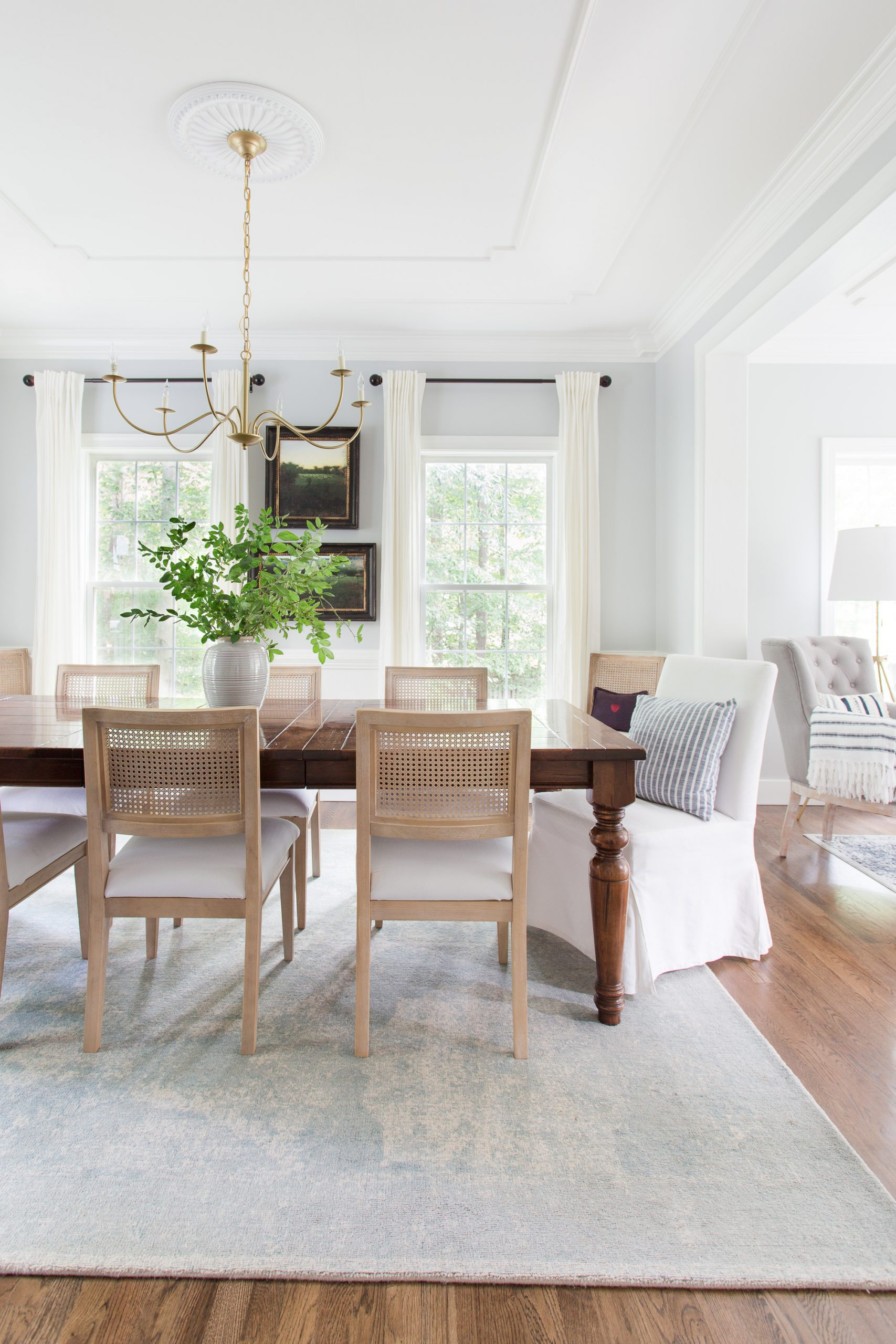 dining room with table, rug, cane chairs with a brass chandelier
