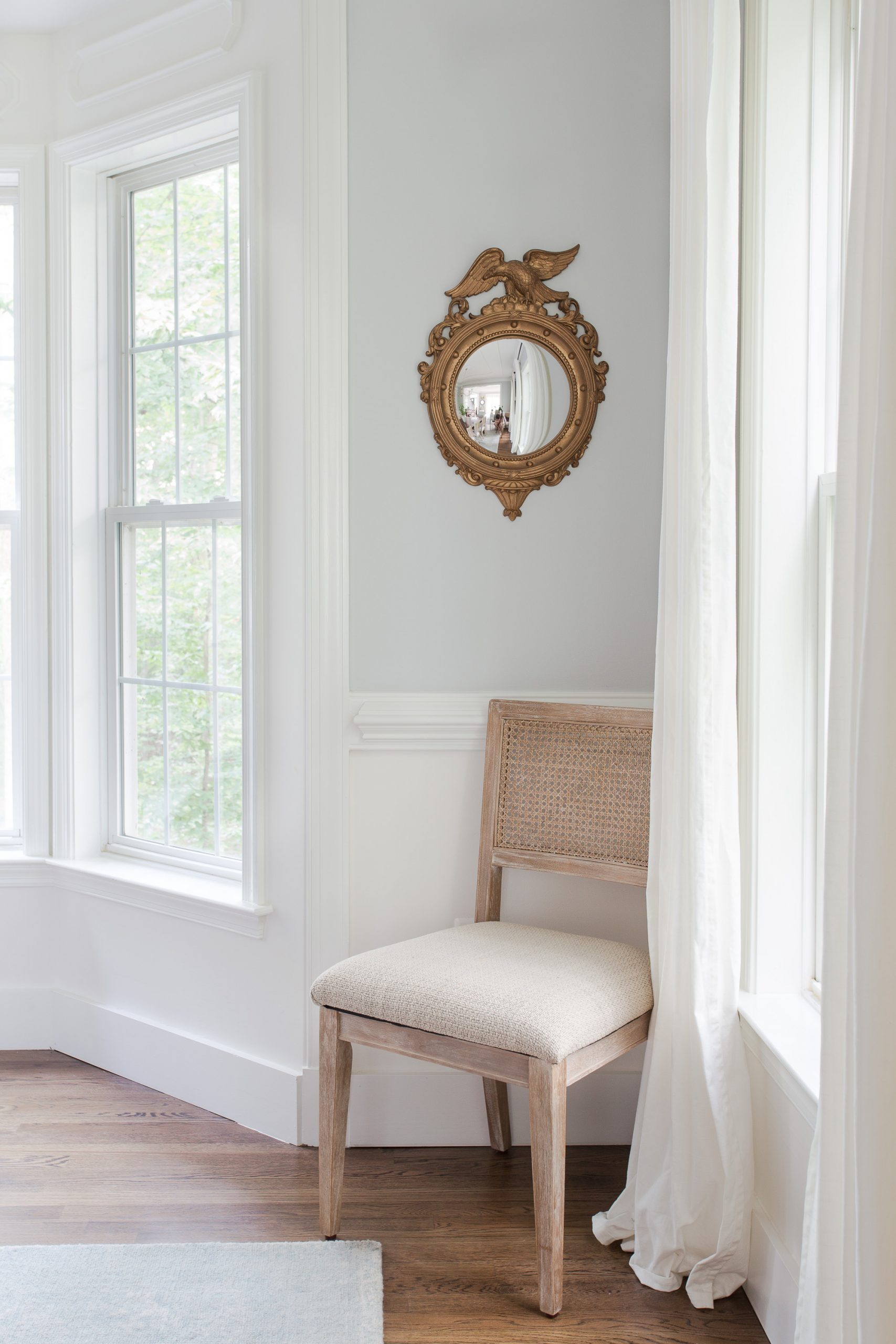 round gold mirror hanging on wall with a chair sitting underneath