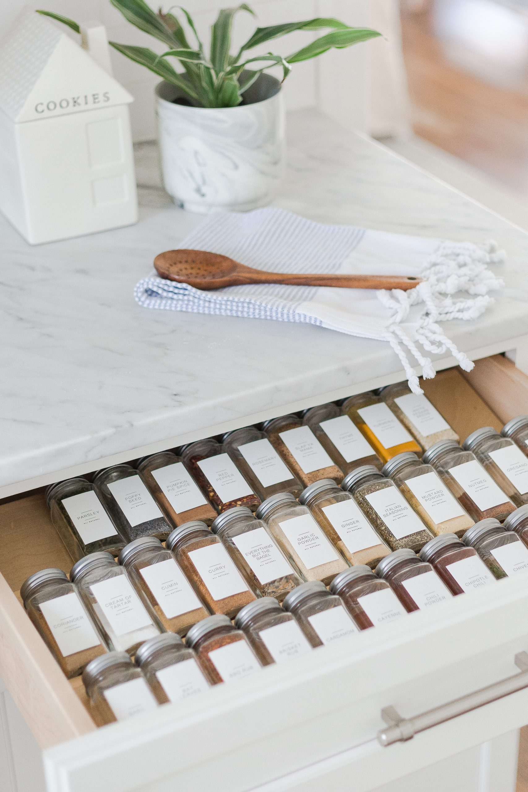 white kitchen with drawer full of spices in clear jars