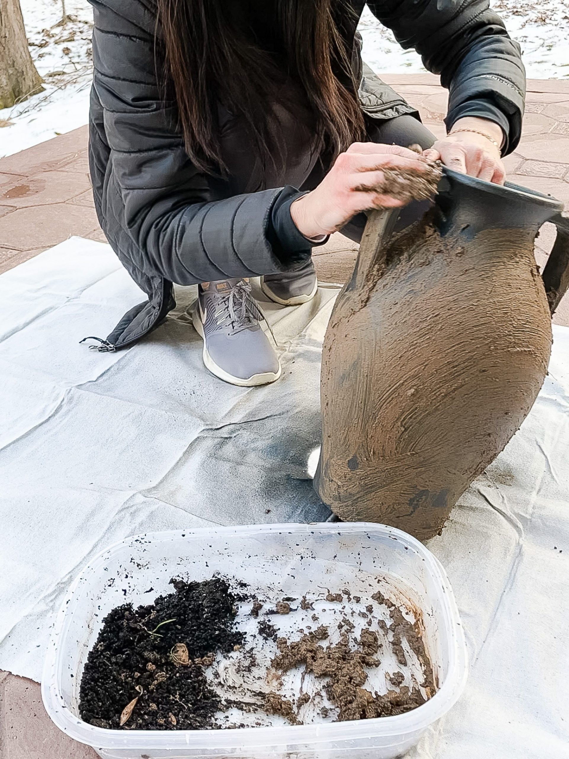 putting dirt on a black pot