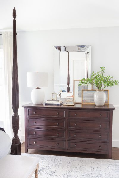 Dark wood dresser with mirror, lamp, books and vase with greenery