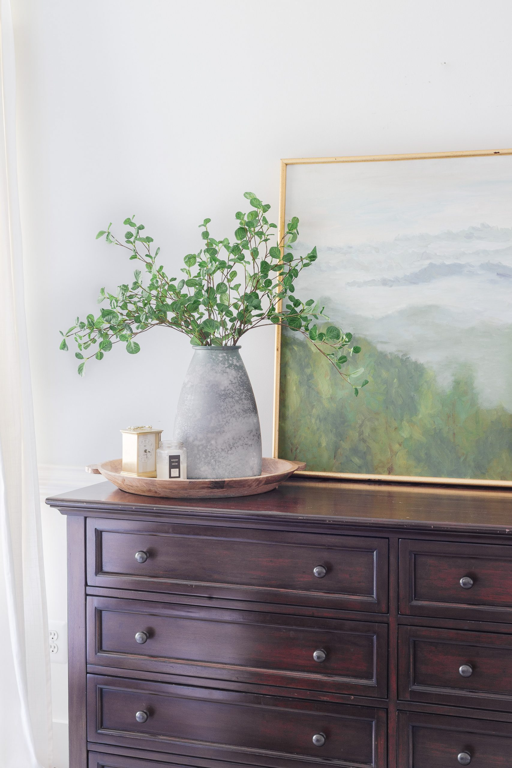 blue vase with greenery on top of a dresser
