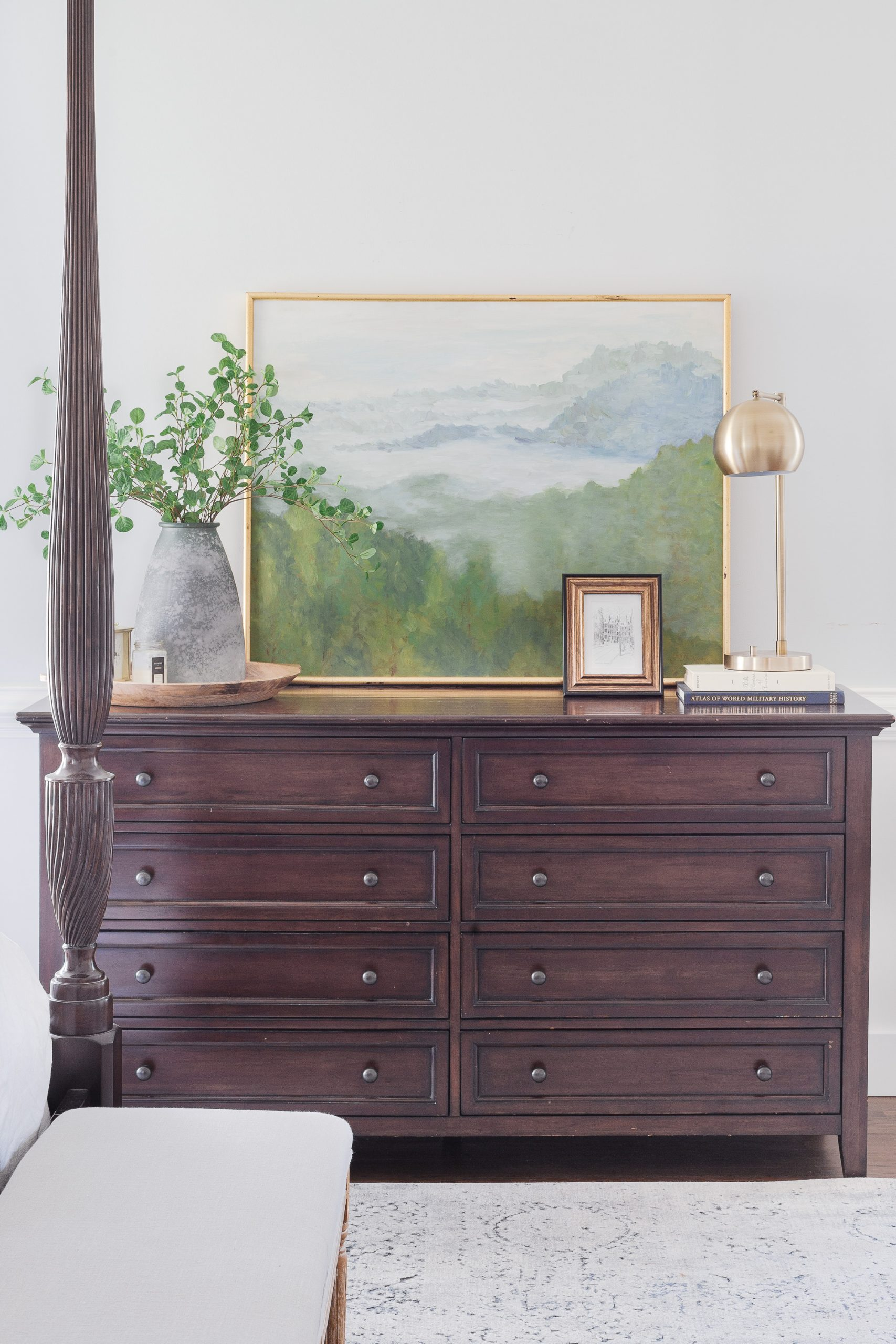 dark wood dresser in bedroom with painting, lamp and vase with greenery on top