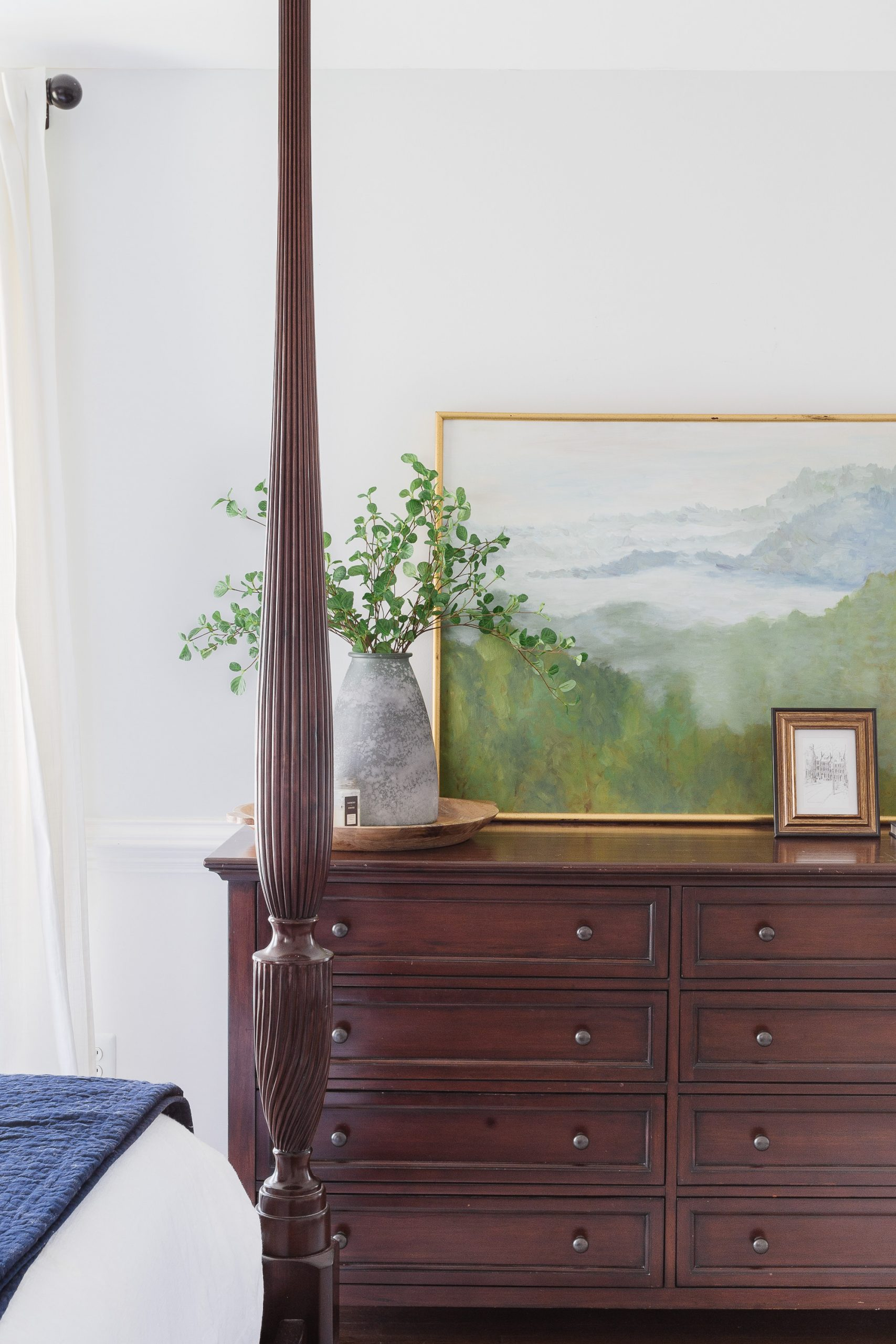 dark wood dresser with painting and vase with greenery