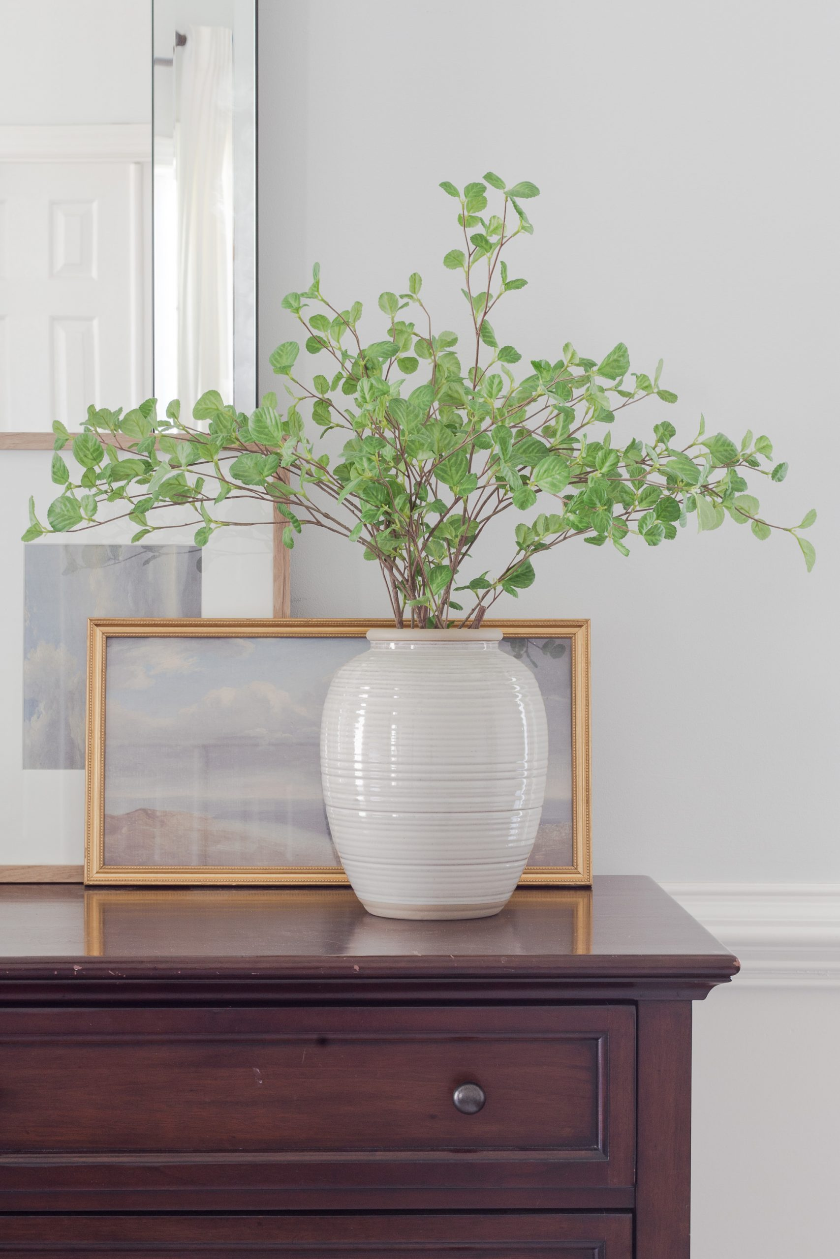 vase with greenery on a wooden dresser with mirror