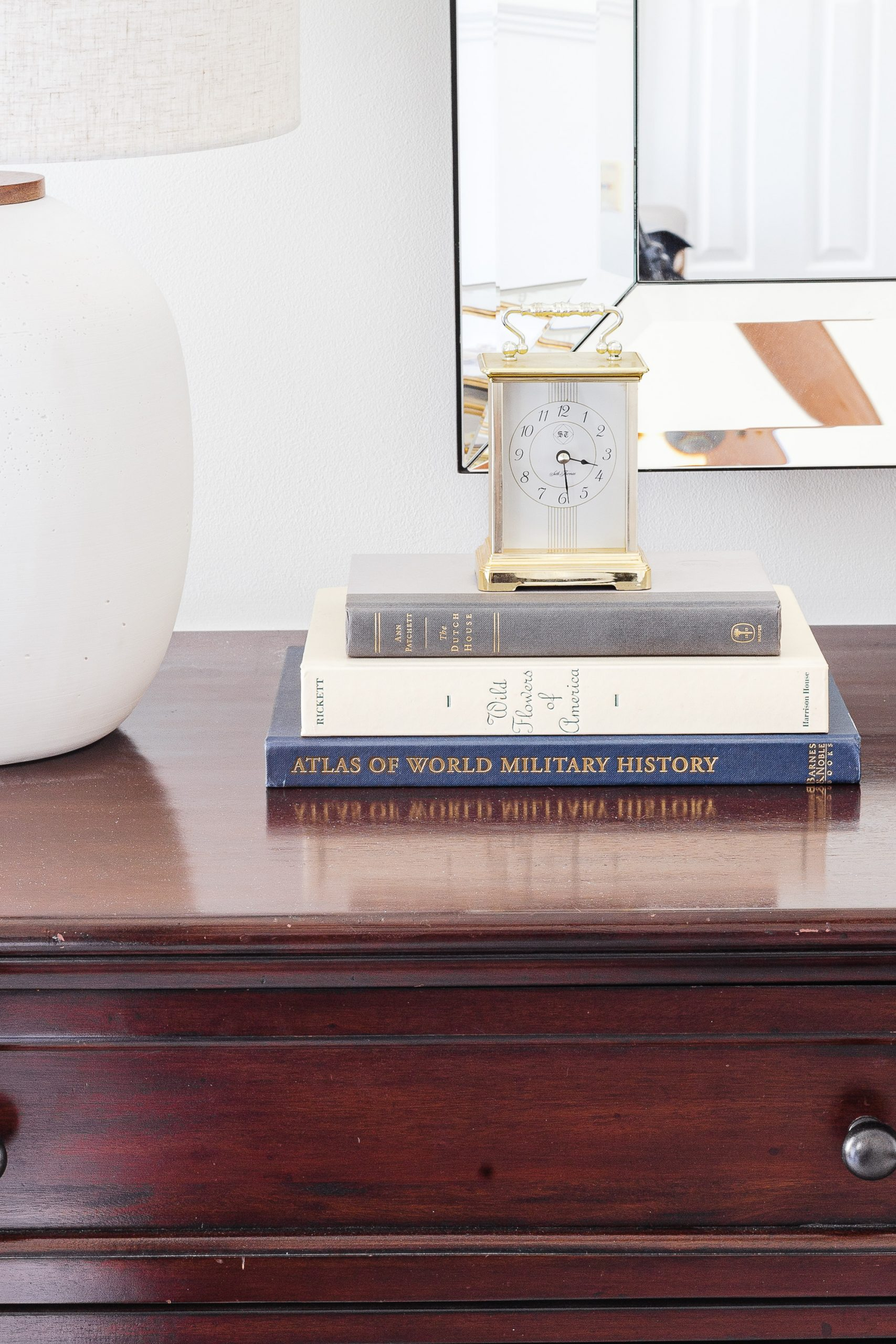 books stacked with a clock on a wooden dresser