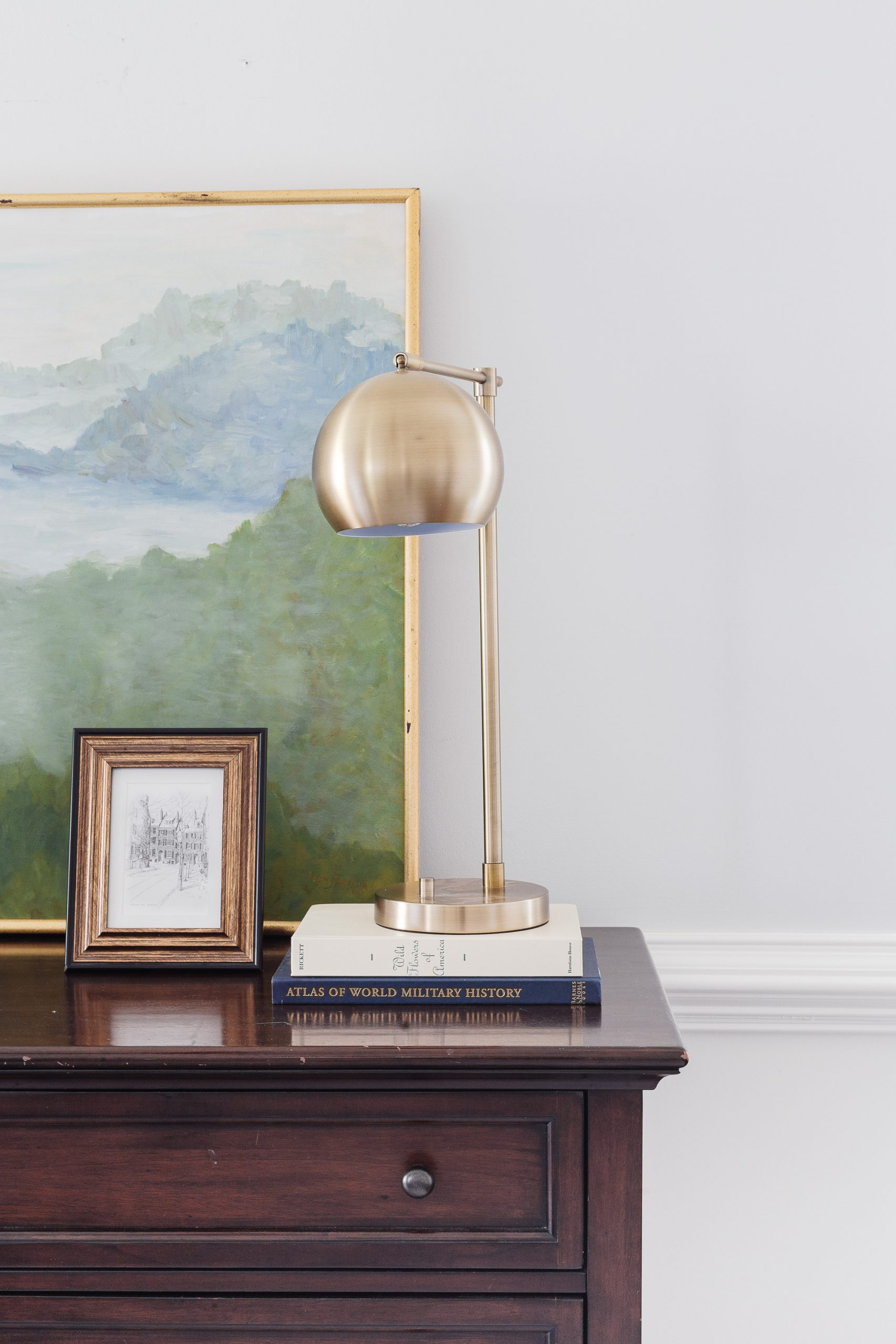 brass lamp sitting on top of books on top of a wooden dresser